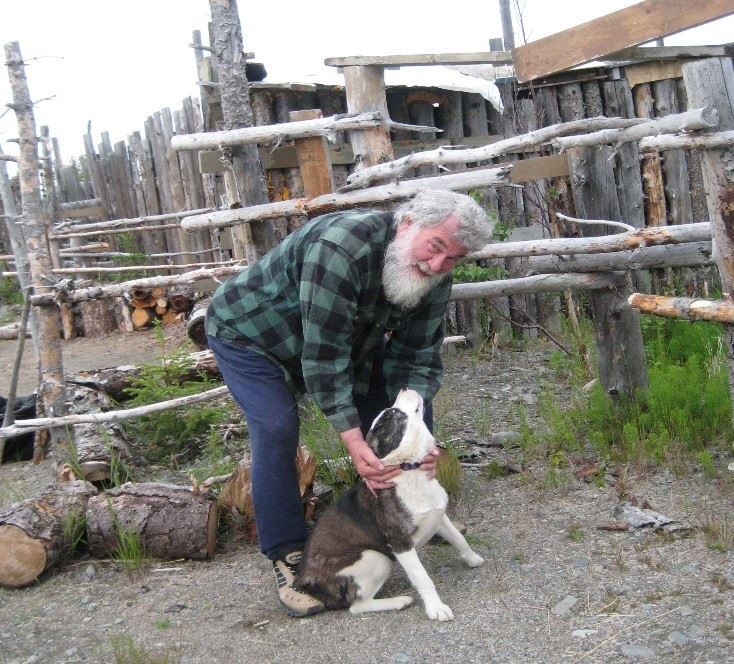 Photo of man and dog in front of a wooden fence