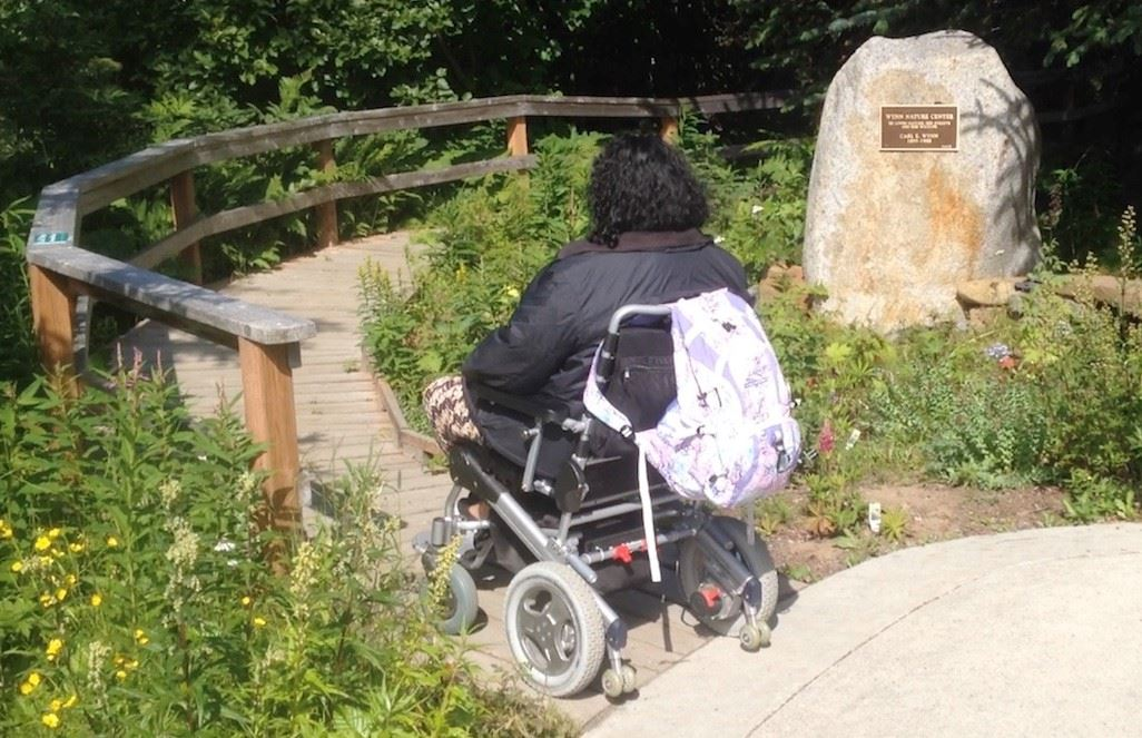 Wheelchair rider entering boardwalk at Wynn Nature Center